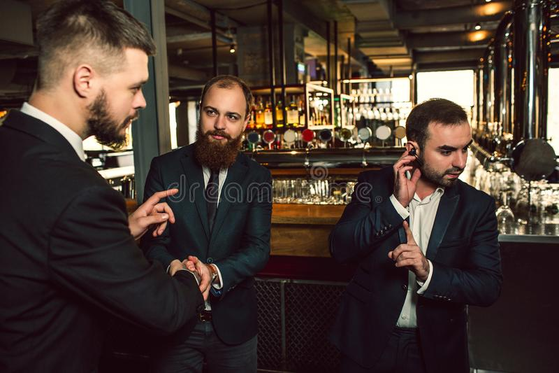 Trois jeunes hommes se tiennent dans le bar Une main de prise sur l'écouteur Il montrent le doigt  Deuxième regard de jeune homme photographie stock libre de droits