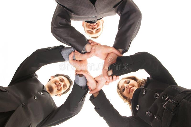 Trois jeunes personnes d'affaires dans une prise de contact de groupe photos stock
