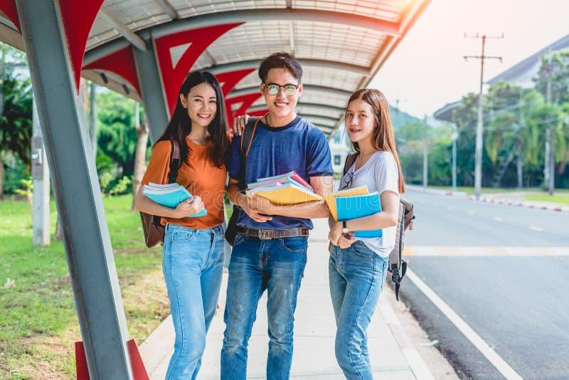 Trois jeunes ?tudiants asiatiques de campus appr?cient le soutien scolaire et la lecture huent image stock