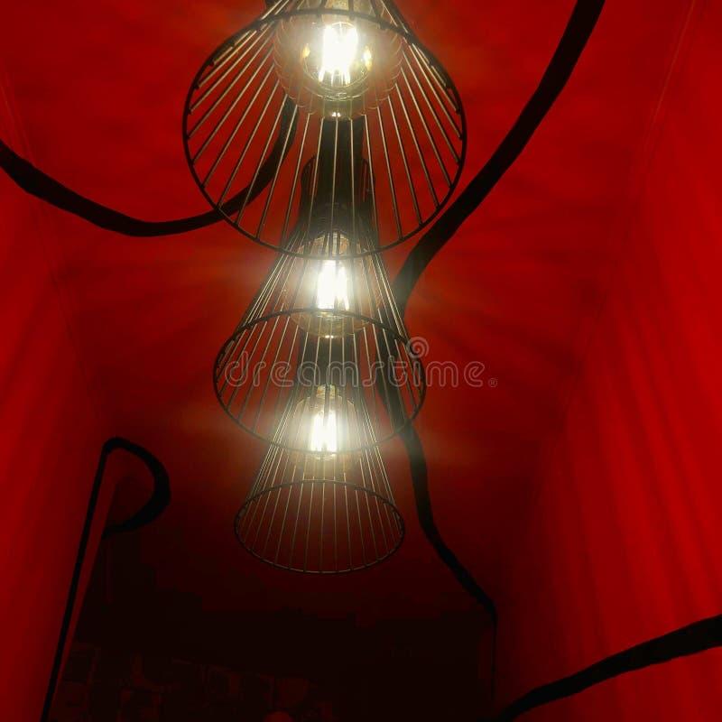 trois lampes noires sur le mur rouge, fond rouge photos stock