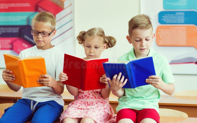 Trois livres de lecture d'écoliers à l'école photographie stock