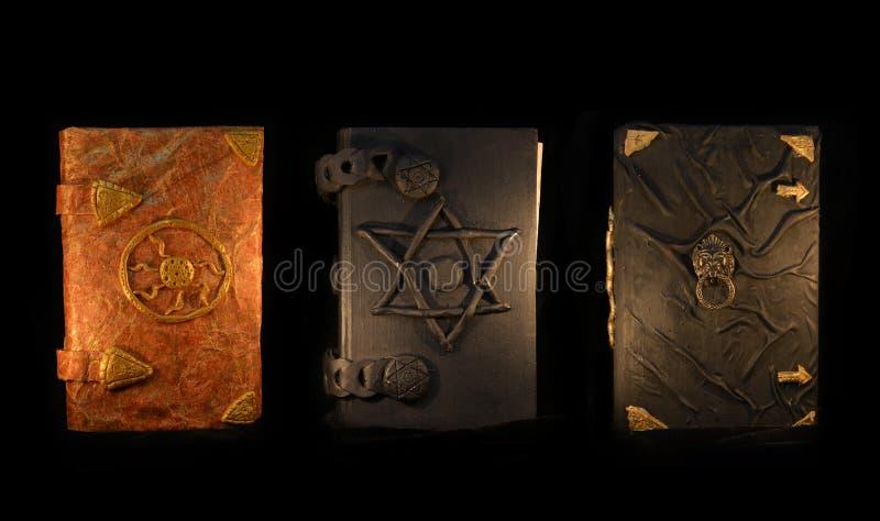 Trois livres de magie noire dans l'obscurité images libres de droits
