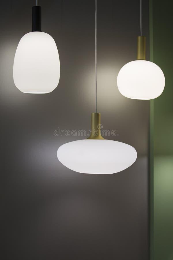 Trois lustres en forme différente, lumières pendantes blanches mates Ovale et rond blancs minimalistic de lustres de conception s image libre de droits