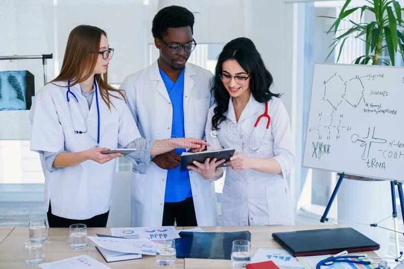 Trois médecins internationaux discutant le rayon X de poumons du patient sur le fond de chambre d'hôpital Concept de soin de Heal photos stock