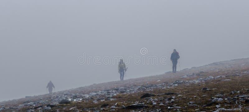 Trois marcheurs traversant l'arête de montagne en brouillard dans l'écossais Highl photos stock