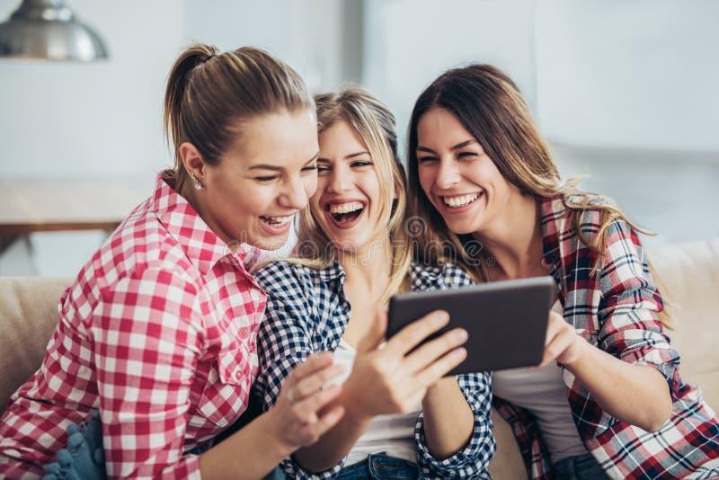 Trois meilleurs amis à l'aide du comprimé numérique ensemble image libre de droits