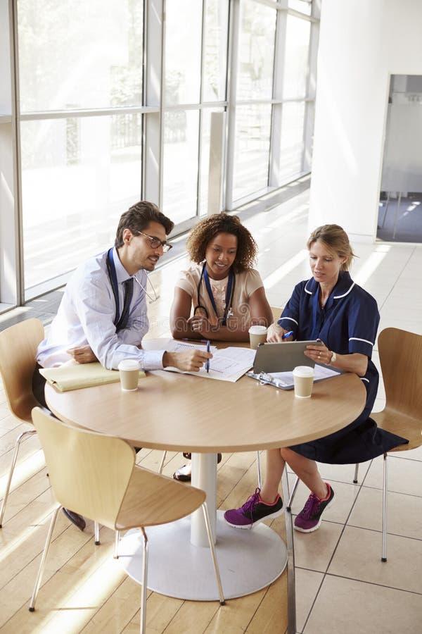 Trois membres du personnel soignant supérieurs lors d'une réunion, courbe photographie stock