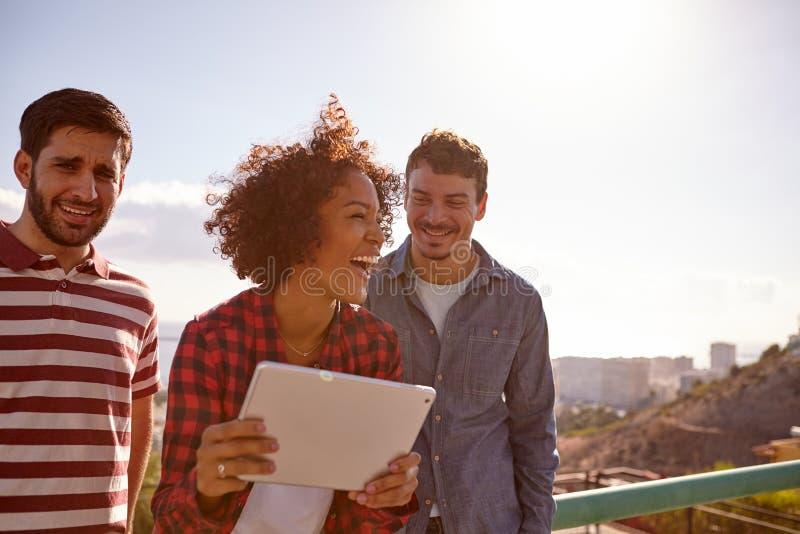 Trois millennials riants avec un comprimé photographie stock libre de droits