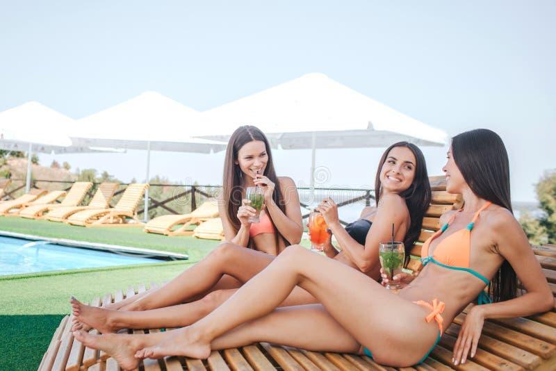 Trois modèles se reposant et se trouvant sur des lits pliants Ils refroidissent Les jeunes femmes boivent des cocktails et ont le photos stock