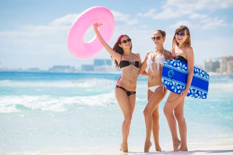 Trois modèles sur une plage tropicale avec un cercle image libre de droits