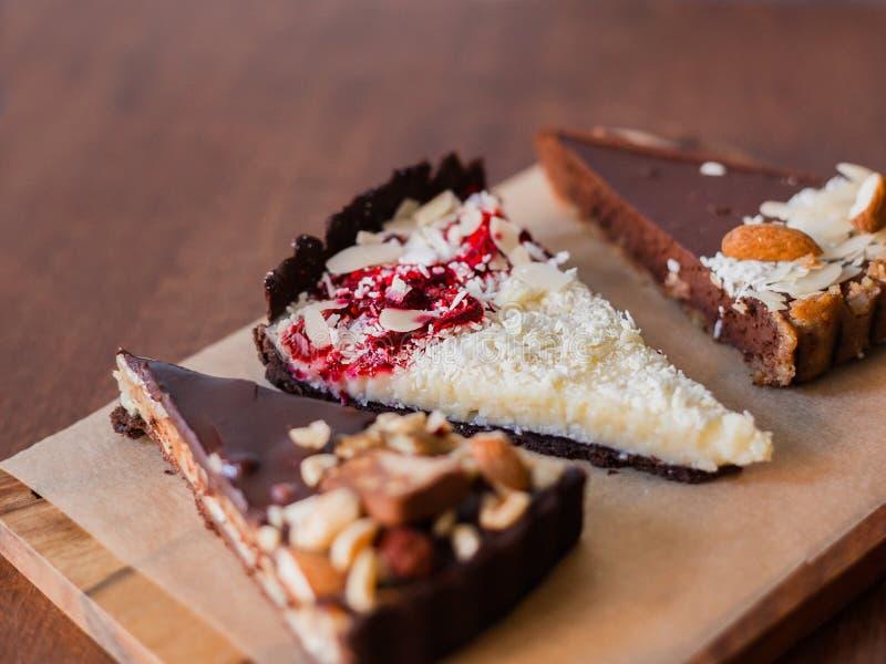 Trois morceaux de gâteau différents sur un conseil en bois, gâteau de noix de coco, 'brownie' d'amande, tarte aux noix de pécan images libres de droits