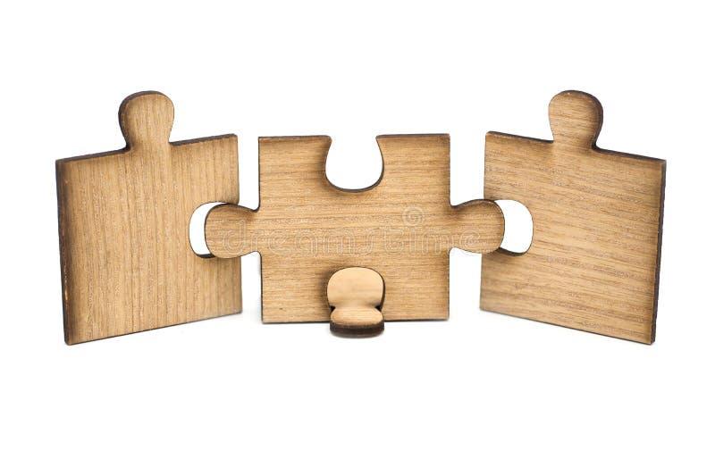 Trois morceaux de puzzle en bois sont reli?s ensemble d'isolement sur le fond blanc Concept de se relier image stock