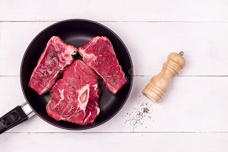 Trois morceaux de viande de boeuf fraîche crue Steak on Pan White Wooden Arrière-plan Haut de la page Voir la copie de l'espace P image libre de droits