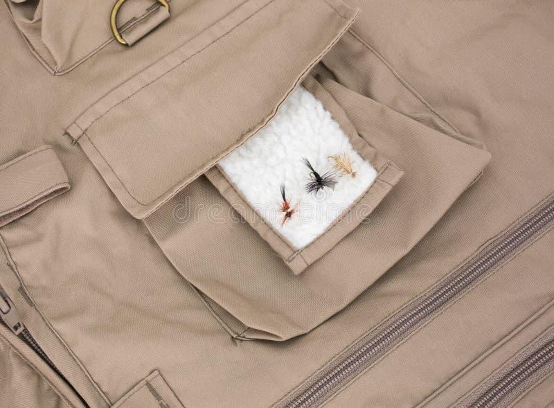 Trois mouches de pêche de mouche sur la correction d'ouatine avec le gilet photographie stock libre de droits