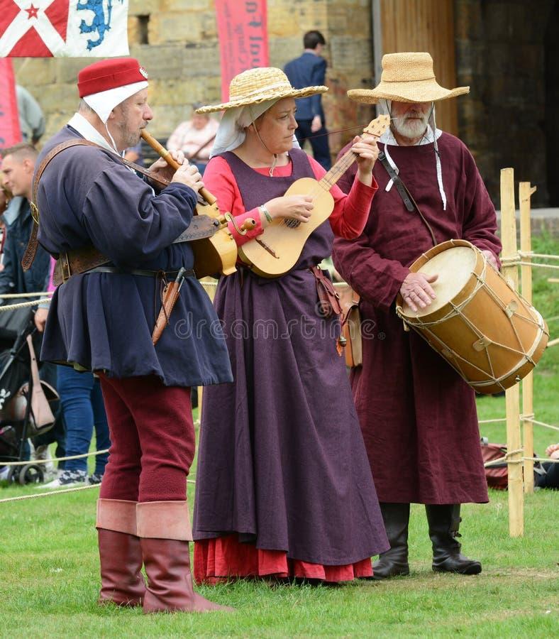 Trois musiciens exécutent à une foire dans le costume médiéval photo libre de droits