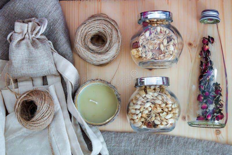 Trois navires en verre avec le thé de fleur, un fil de ficelle, une bougie, un sac de toile et un mensonge de sac d'eco sur un ti photographie stock