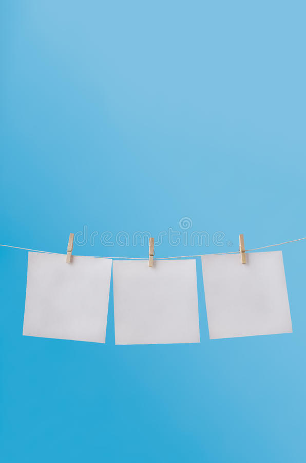 Trois notes en blanc chevillées sur la ligne de lavage en ciel bleu images stock