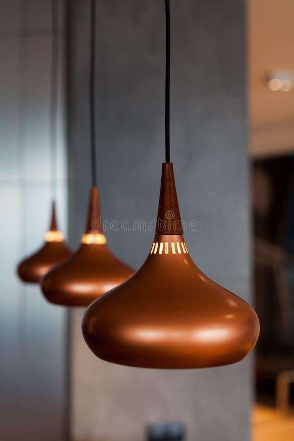 Trois nouvelles lampes faites de cuivre ont suspendu du plafond dans la salle à manger photos libres de droits