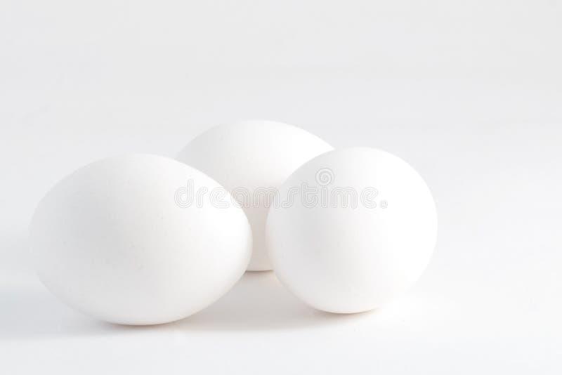 Trois oeufs blancs d'isolement sur le fond blanc image stock