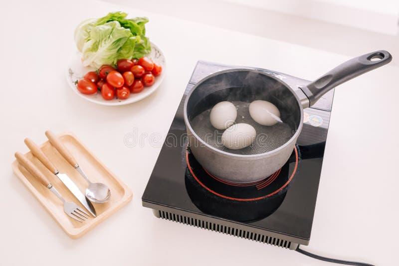 Trois oeufs bouillant dans la casserole de l'eau image libre de droits