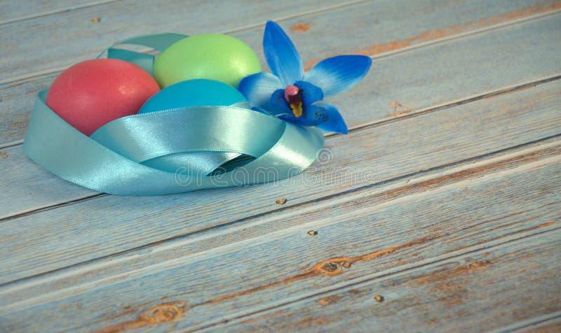 Trois oeufs de pâques avec un ruban bleu de satin et un bourgeon d'orchidée sur une table en bois photos stock
