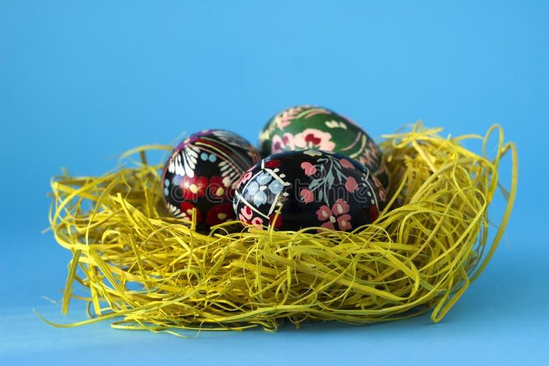 Trois oeufs de pâques décorés se situent dans un nid de foin sur un fond bleu Oeufs de pâques d'Ukrainien avec des ornements et d photographie stock libre de droits