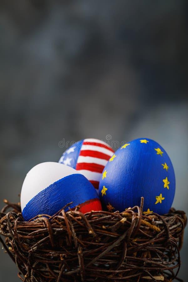 Trois oeufs de pâques dans un nid peint en couleurs des drapeaux de la Russie, de l'Amérique et de l'Union européenne photo stock