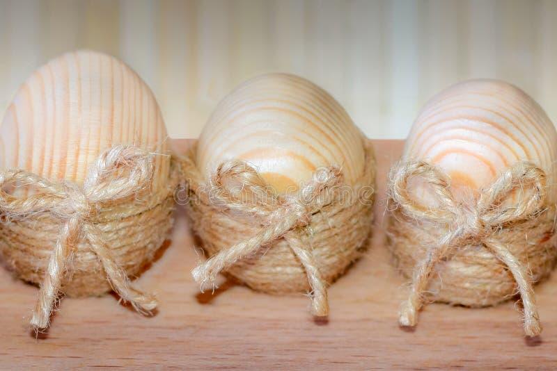 Trois oeufs de pâques enveloppés en ficelle sous forme de nid sur un fond en bois photographie stock