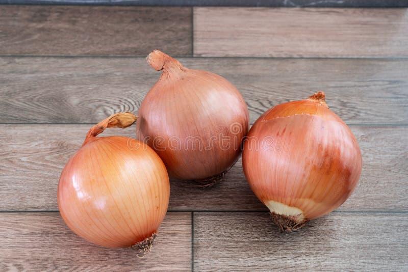Trois oignons sur le plancher en bois photo stock