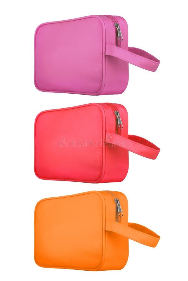 Trois ont coloré les couleurs de sacs de voyage, rouges et oranges cosmétiques en cuir, d'isolement sur le fond blanc chemins de  photos libres de droits