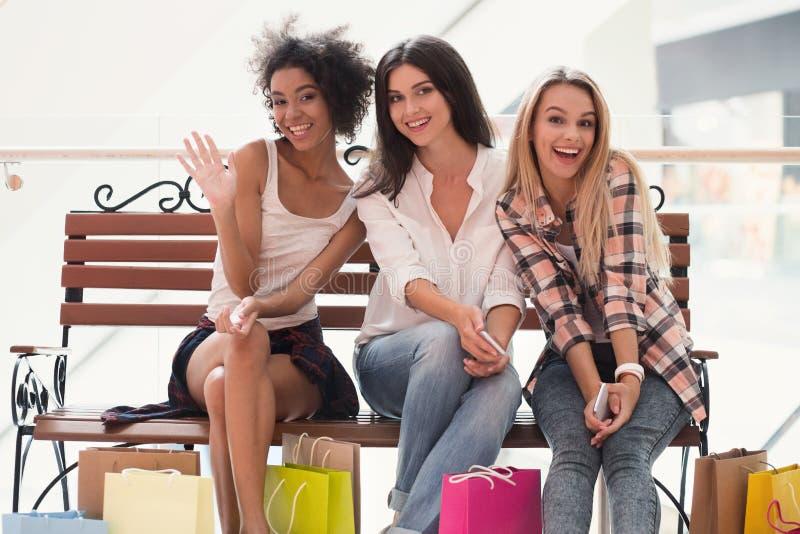 Trois ont excité la femme se reposant sur le banc au centre commercial images libres de droits