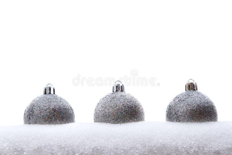Trois ornements argentés de Noël de scintillement dans la neige images libres de droits