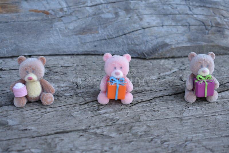 Trois ours de jouet avec des cadeaux sur le conseil photos stock