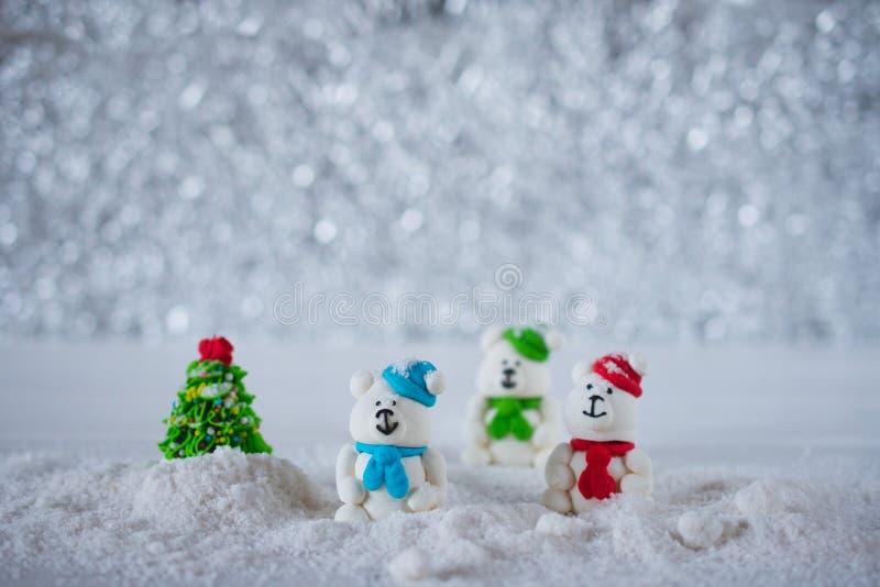 Trois ours de sucrerie de sucre dans la neige sur le fond de bokeh avec l'espace de copie pour la salutation de saison photo libre de droits