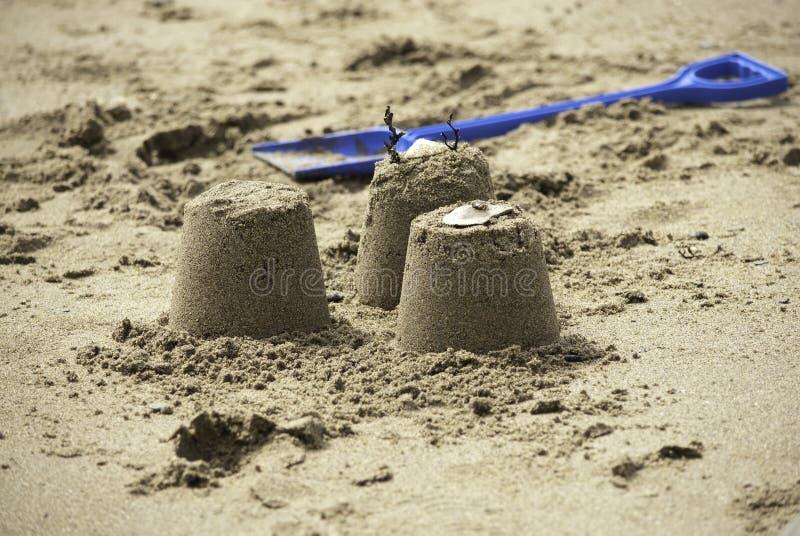 Trois pâtés de sable simples avec la pelle bleue photo stock