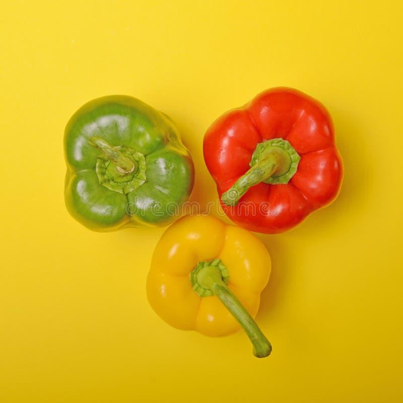 Trois paprikas colorés sur le fond jaune - vue étendue plate minimale images stock