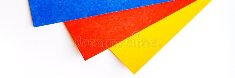 Trois parts de feuilles colorées sur le fond blanc Carton vide bleu, rouge et jaune Concept pour la page drapeau images stock