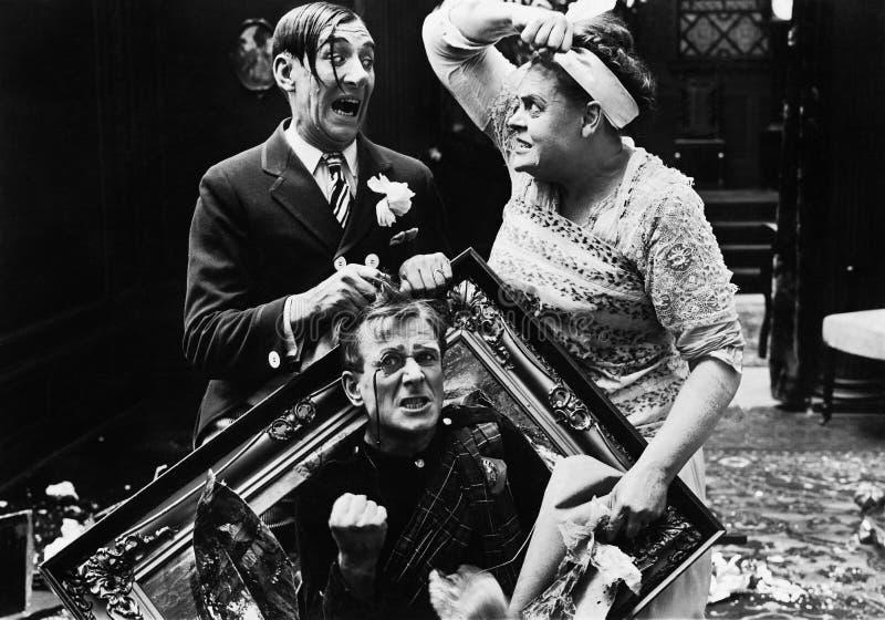 Trois personnes à la maison combattant les uns avec les autres (toutes les personnes représentées ne sont pas plus long vivantes  photographie stock