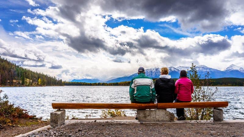 Trois personnes appréciant la vue du lac pyramid en Jasper National Park photographie stock