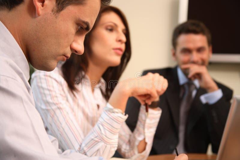Trois personnes d'affaires collaborant avec l'ordinateur portatif dans le bureau ensoleillé photographie stock