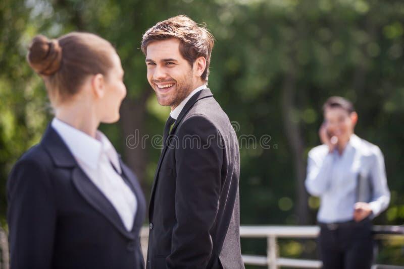 Trois personnes heureuses d'associé parlant dehors images stock