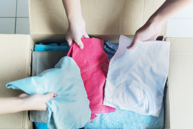 Trois personnes mettant des vêtements dans une boîte en carton photos libres de droits
