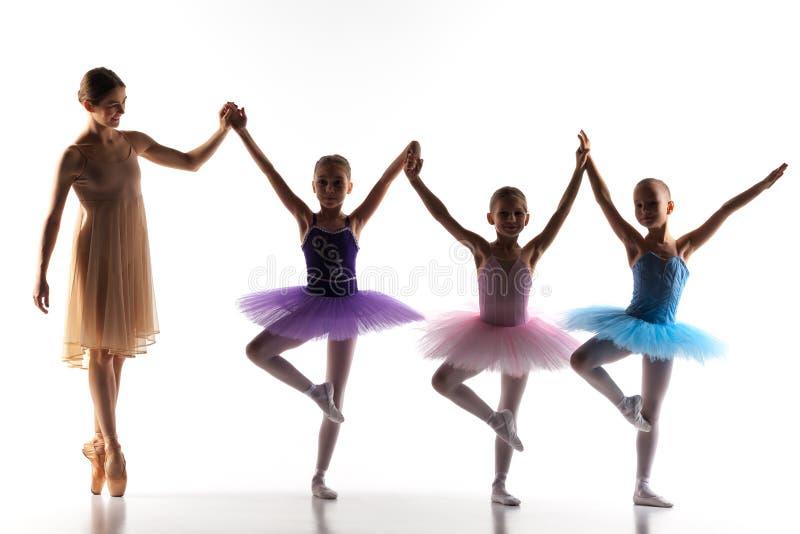 Trois petites ballerines dansant avec le professeur personnel de ballet dans le studio de danse image stock