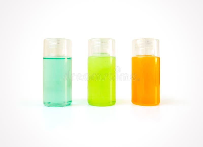 Trois petites bouteilles en plastique complètement de produits cosmétiques colorés photos stock