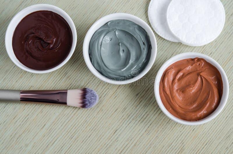 Trois petites cuvettes avec le masque protecteur cosmétique rouge et bleu de chocolat de noir d'argile et de cacao Traitements fa images libres de droits