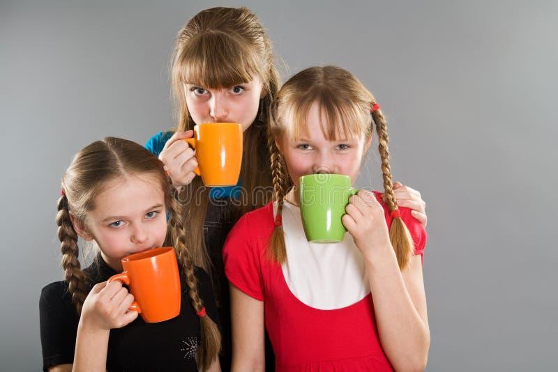 Trois petites filles mignonnes avec des tasses photographie stock