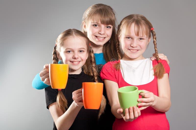 Trois petites filles mignonnes avec des tasses image stock