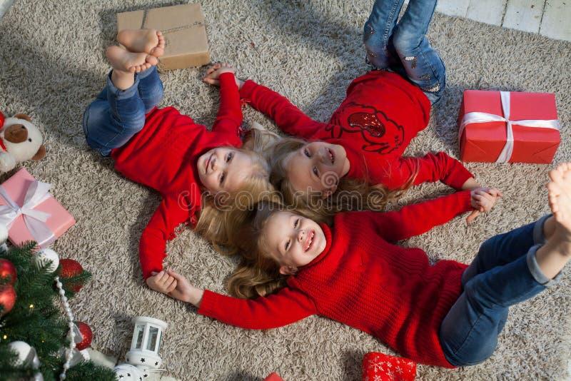 Trois petites filles se trouvent près d'un arbre de Noël avec des vacances de nouvelle année de cadeaux photo libre de droits
