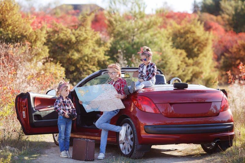 Trois petites filles voyageant en voiture sur une route de campagne dans la nature en été images libres de droits