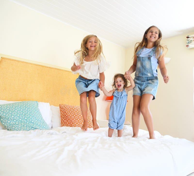 Trois petites soeurs sautant sur un lit photo stock